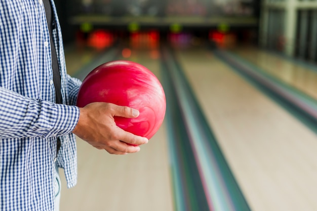 Persona in possesso di una palla da bowling rossa