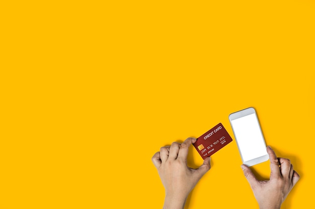 Person holding a red credit card and a mobile phone, images for online shopping advertisements, pay with credit card, isolated on yellow background and clipping path.