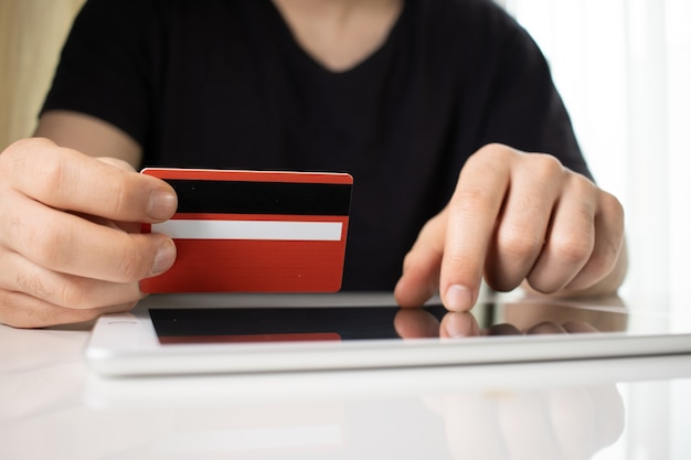 Person holding a red credit card over a tablet on a white surface