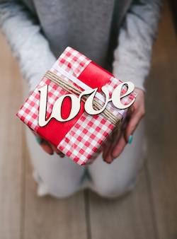 Persona in possesso di regalo rosso con la parola