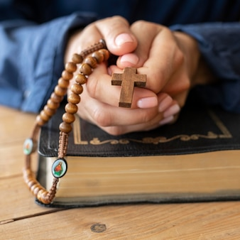 Person holding rosary in hands and praying