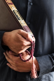 Person holding rosary and religious book Free Photo
