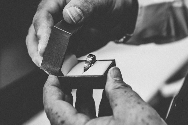 Person holding a silver ring inside of a box