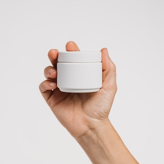 Person holding a skin care product in a blank recipient