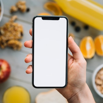 Person holding smartphone with blank screen above fruits