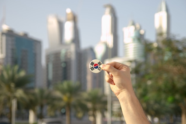 Person holding a south korea flag symbols item in hand in front of skyscrapers