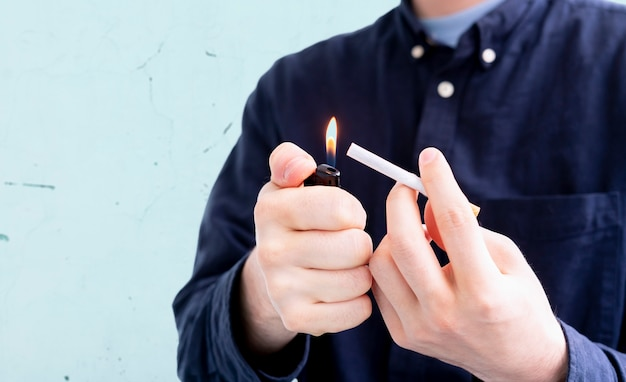 A person holding a spark lighter flame and a cigarette, smoking bad habbit