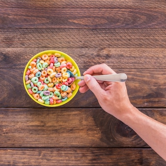 Person holding spoon in bowl of cereal