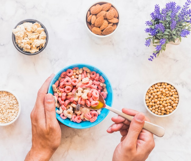Person holding spoon with cereal above blue bowl
