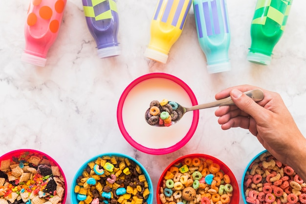 Person holding spoon with cereal above bowl of milk