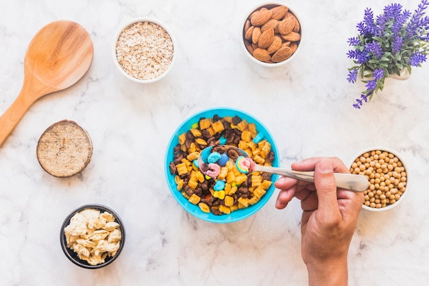 Person holding spoon with cereal above bowl