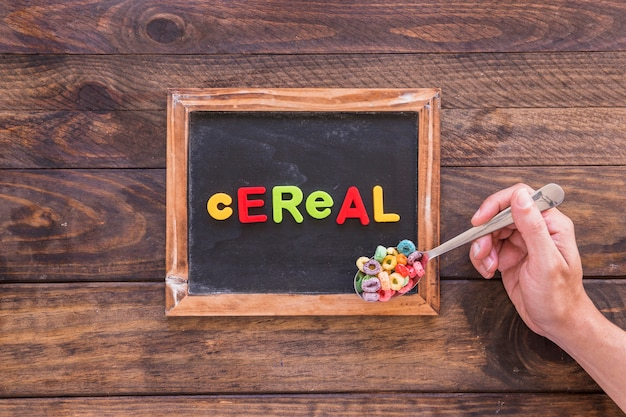 Person holding spoon with cereal above chalkboard
