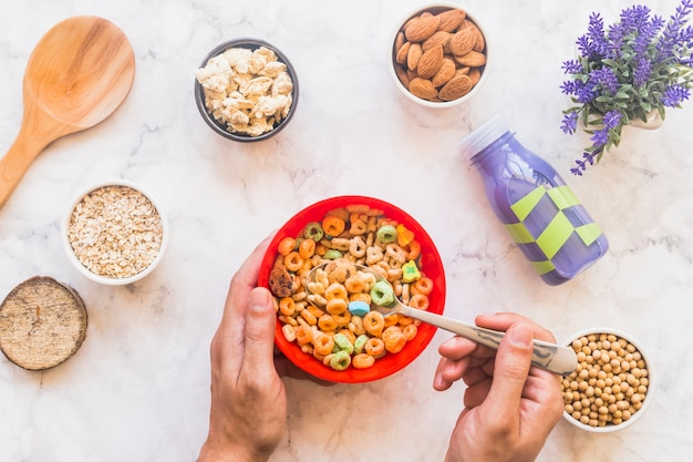 Person holding spoon with cereal above red bowl