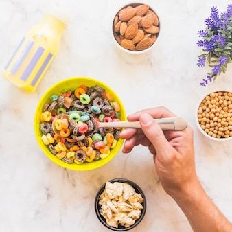 Person holding spoon with cereal above yellow bowl