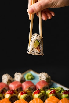 Person holding sushi with chopsticks