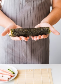Person holding sushi wrap