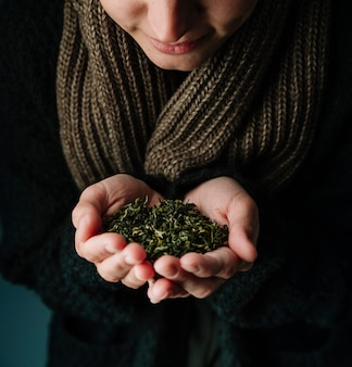 Person holding tea herbs and wearing a scarf