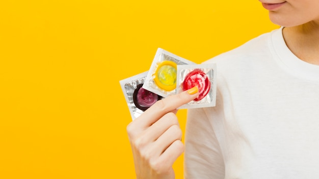 Person holding three different condoms with copy space