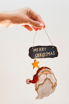 Person holding toy with merry christmas inscription