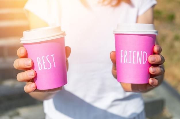 親友のコンセプトで2つのピンクの使い捨てカップを持っている人。