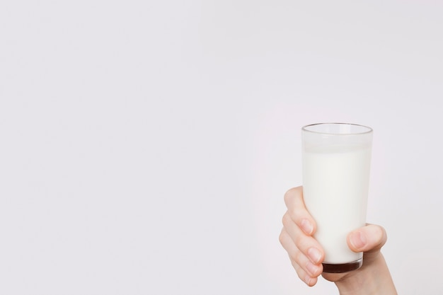 Person holding up a glass of milk with copy space