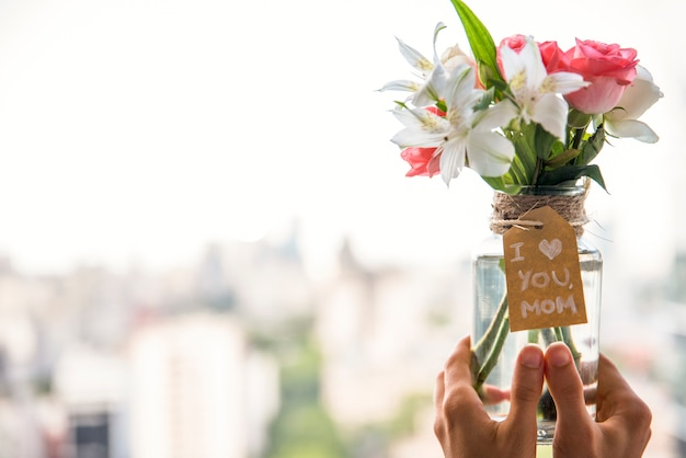 Person holding vase with flowers and i love you mom inscription