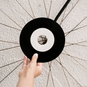 Person holding vinyl record near white wall