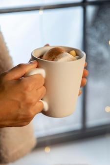 Persona che tiene una tazza bianca di cioccolata calda