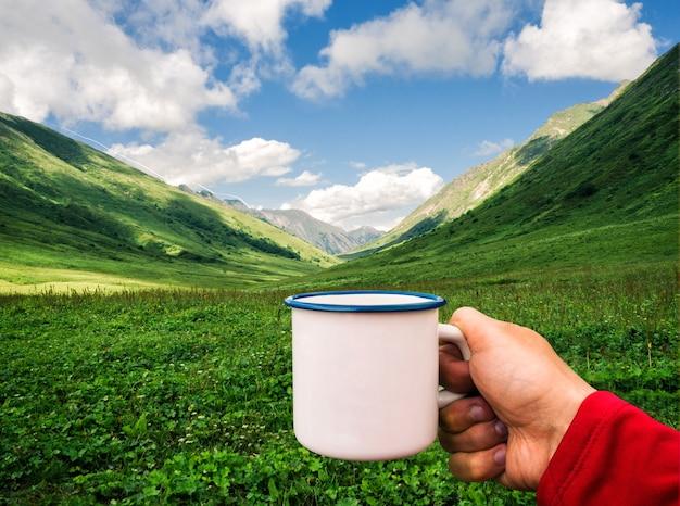 緑の山々の背景で白いエナメルカップを保持している人