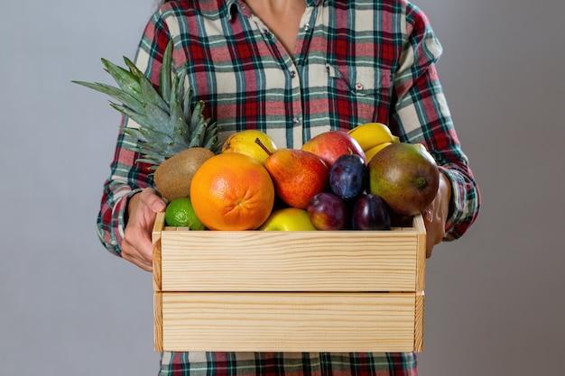 신선한 다채로운 과일로 가득한 나무 상자를 들고있는 사람