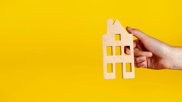 Persona in possesso di una casa in legno con copia spazio