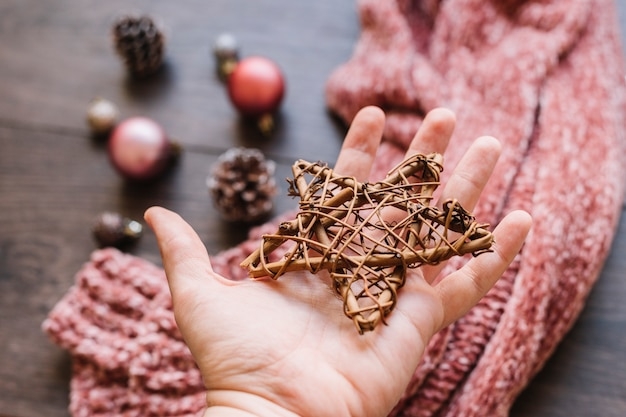 Person holding wooden star in hand