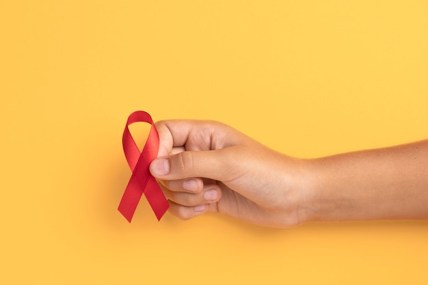 Person holding an world aids day ribbon symbol