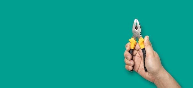 노란색 손잡이 펜치, 손 도구, 녹색 배경 및 클리핑 패스에 격리됨을 들고 있는 사람.