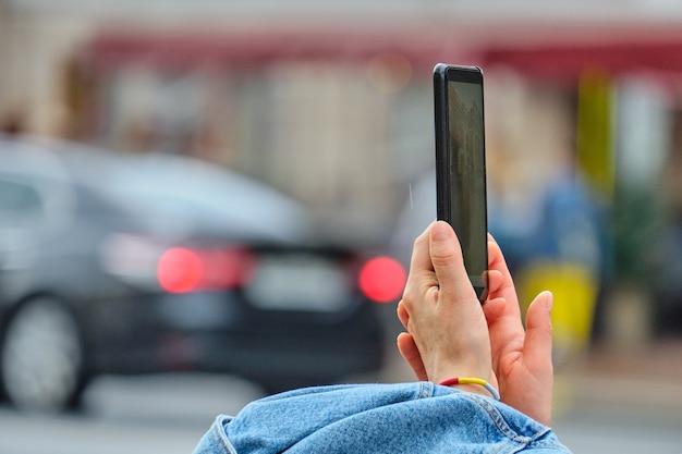 人はスマートフォンを持って街で写真を撮ります。