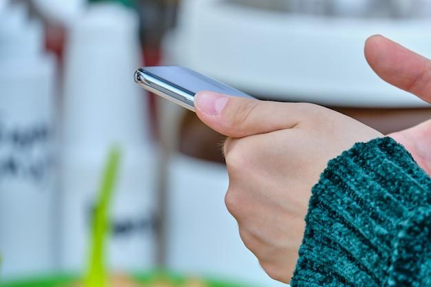 人はスマートフォンを持って使用します。