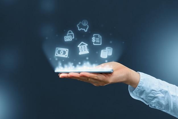 Человек держит смартфон с проекцией иконок мобильного банкинга.