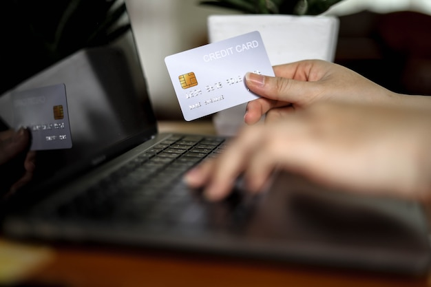 The person holds a credit card and is filling out their credit card information to pay for goods online, credit cards can pay for goods and services both in the storefront and online shopping.
