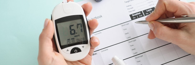 Person holds glucometer with blood sugar readings and makes notes in notebook