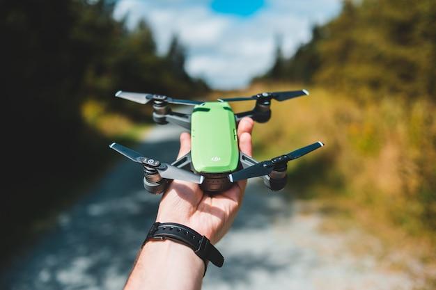 La persona detiene drone verde e nero