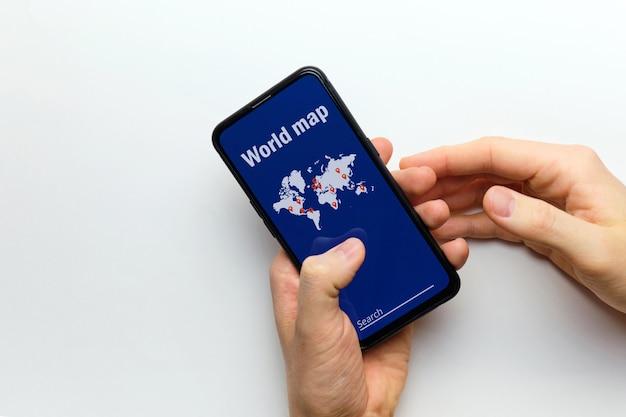 사람은 검색과 함께 세계지도와 스마트 폰을 손에 들고 있습니다.