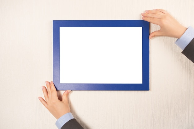 Person holds mockup picture frame on the wall