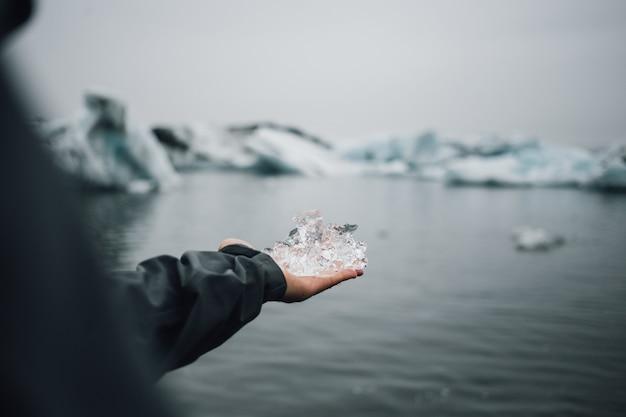 La persona tiene il pezzo di ghiaccio del ghiacciaio in islanda