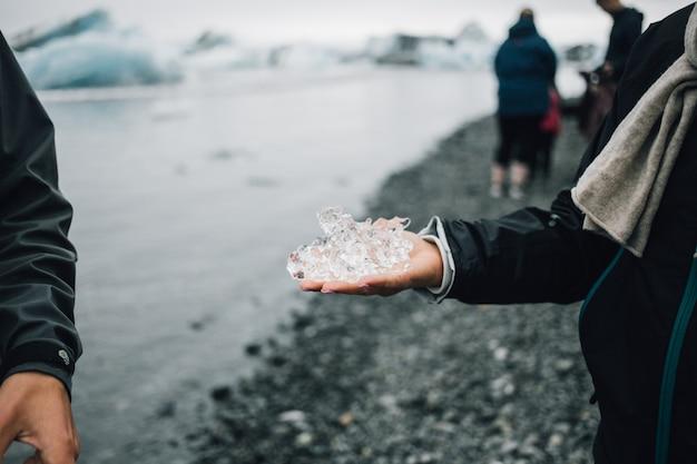 Человек держит кусок ледникового льда в исландии