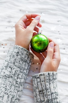 Person holds sparkling green christmas ball