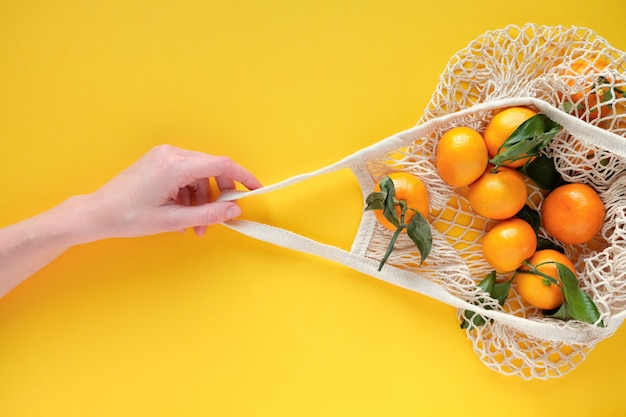 Person holds a string bag with tangerines