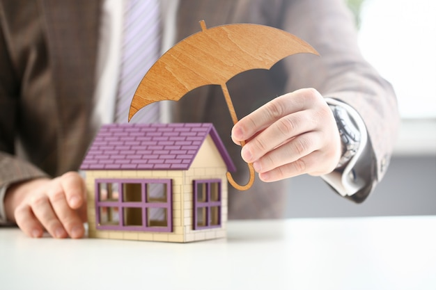 Person holds wooden umbrella over house