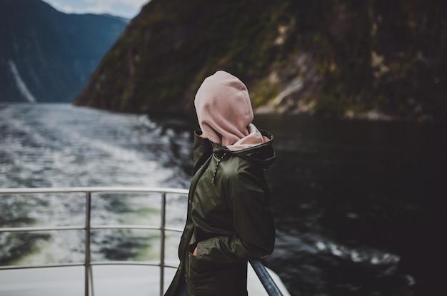 Persona in felpa con cappuccio in piedi sulla nave durante la crociera a milford sound in nuova zelanda