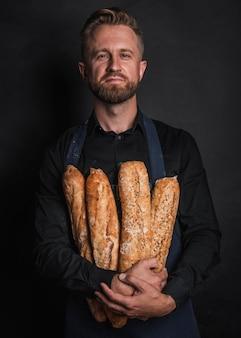 Человек обнимает буханки хлеба, вид спереди