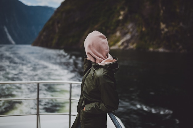 ニュージーランドのミルフォードサウンドでのクルーズ中に船の上に立っているパーカーの人